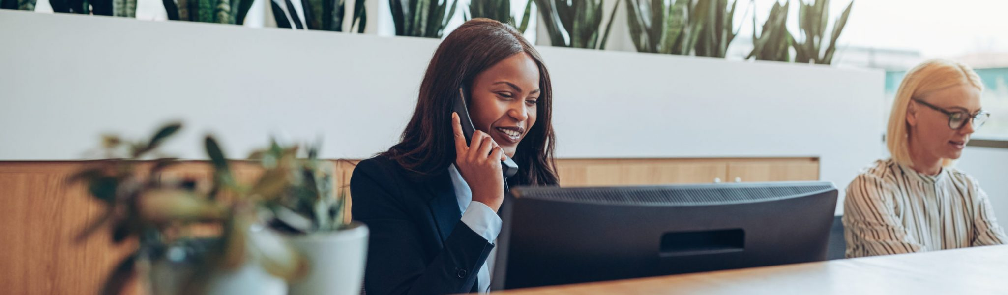 Smiling young African American businesswoman talking on the telephone while working with a colleague at an office reception desk